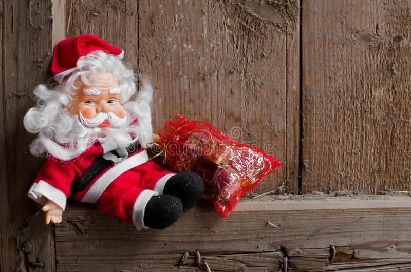Toy Santa Claus and bag with Christmas gifts on vintage wooden background. stock image
