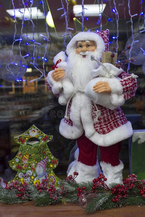 Toy Santa Claus with Christmas decor on the windowsill of a store in the city of Lutsk, Ukraine. Toy smiling pretty Santa Claus with Christmas decor on the stock photos