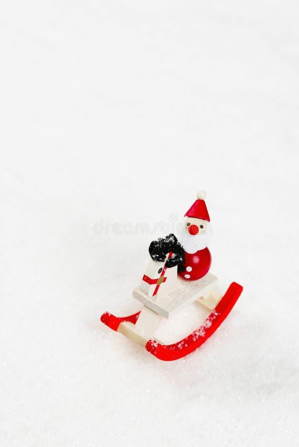 Toy Santa Claus con il cavallo a dondolo su un mucchio della neve fotografia stock
