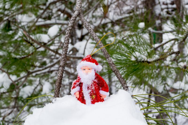 Toy Santa Claus in the snow. In the winter season, christmas, background, gift, new, year, decoration, car, red, holiday, white, xmas, merry, isolated, hat royalty free stock photo