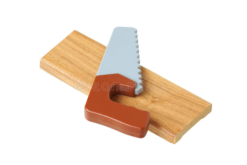 Toy saw on a piece of wood. Islated royalty free stock photo