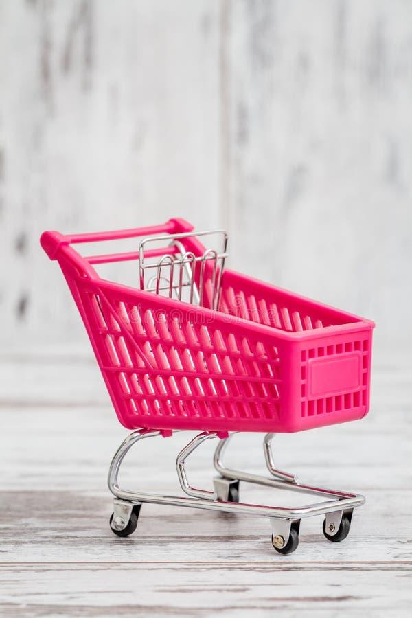 Toy Shopping Cart cor-de-rosa diminuto no fundo branco imagens de stock
