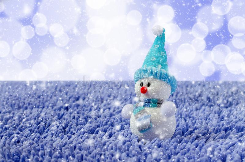 Toy Snowman with hat and scarf. Falling snow royalty free stock photo
