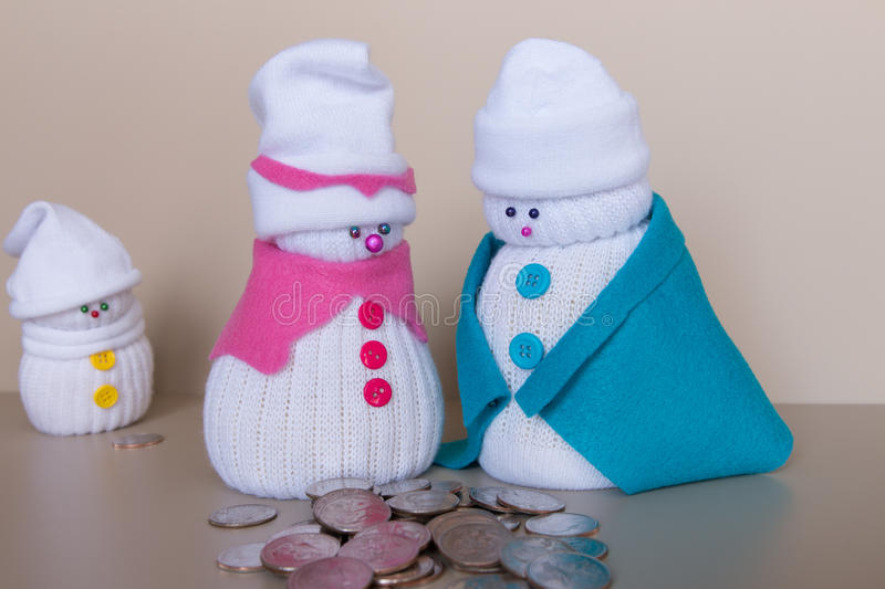 Toy snowmen family and a pile of quaters stock photos