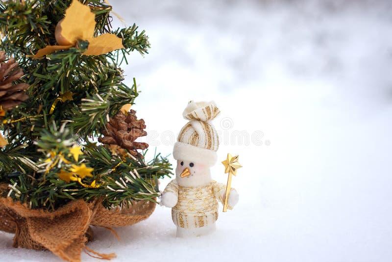 Toy snowmen. Snowmen in the winter woods near a Christmas tree stock image