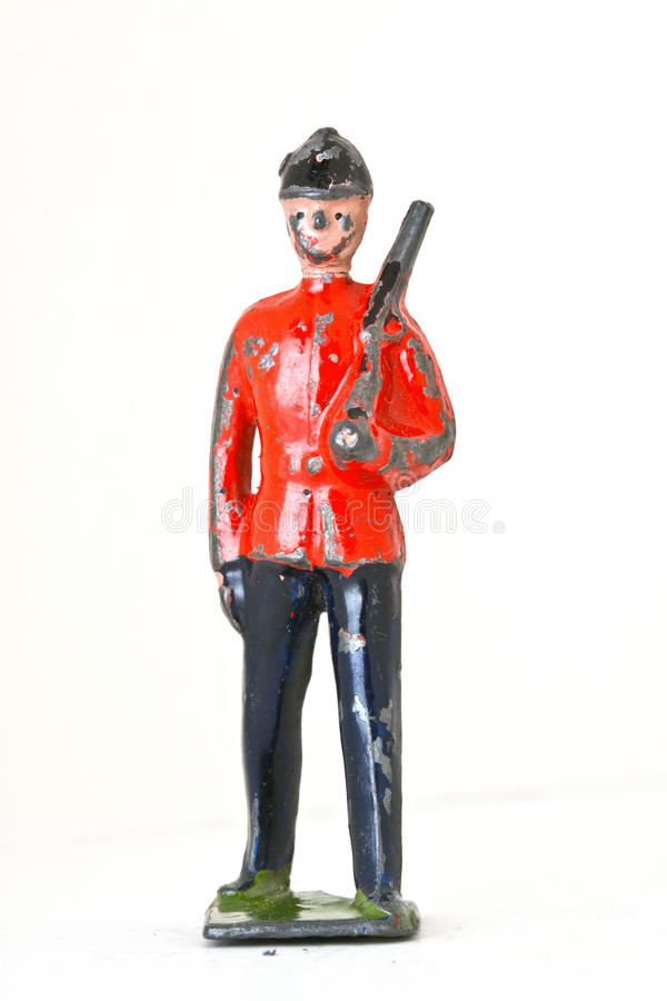 Toy soldier with rifle - Foot guard frontview. Vintage toy soldier poses with rifle isolated on white background stock image