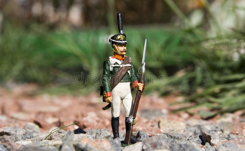 Toy soldier among the rocks. Closeup photo of the toy soldier placed on a gravel in the garden stock photo