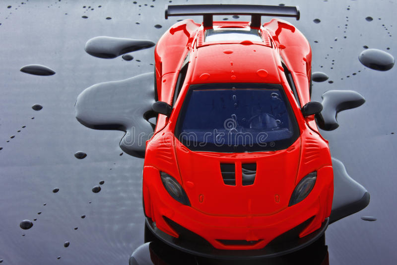 Toy Sports car. Toy red sports car isolated over water drops background stock photos