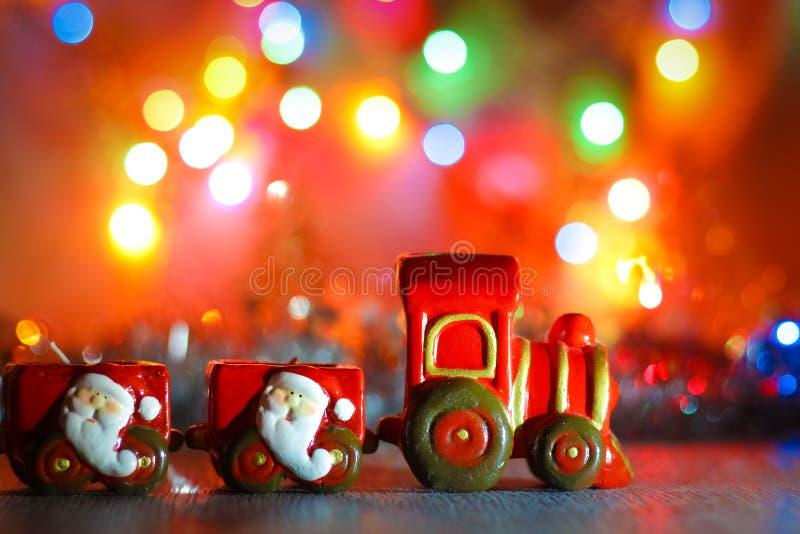 Toy Steam Train mit Santa Claus auf einem Hintergrund von goldenen Girlanden und Unschärfe von farbigen Lichtern lizenzfreies stockbild