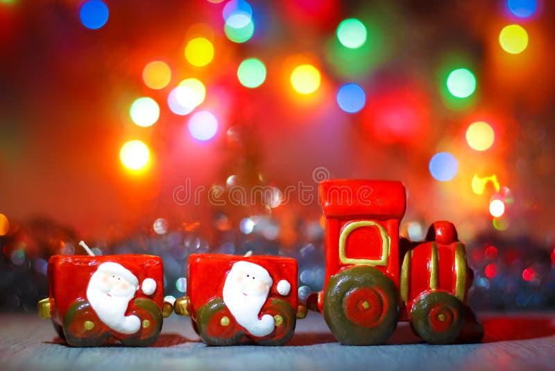 Toy Steam Train mit Santa Claus auf einem Hintergrund von goldenen Girlanden und Unschärfe von farbigen Lichtern lizenzfreie stockfotos