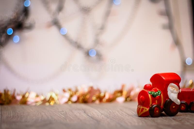 Toy Steam Train mit Santa Claus auf einem Hintergrund von goldenen Girlanden und Unschärfe von farbigen Lichtern lizenzfreie stockfotografie