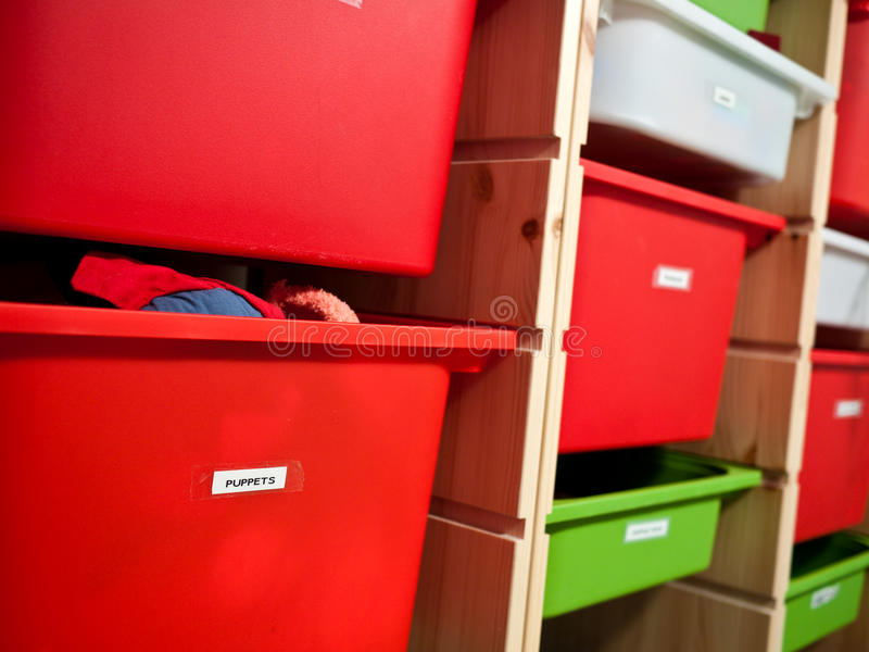 Toy storage. Labelled bins for toy storage with focus on front bin for puppets