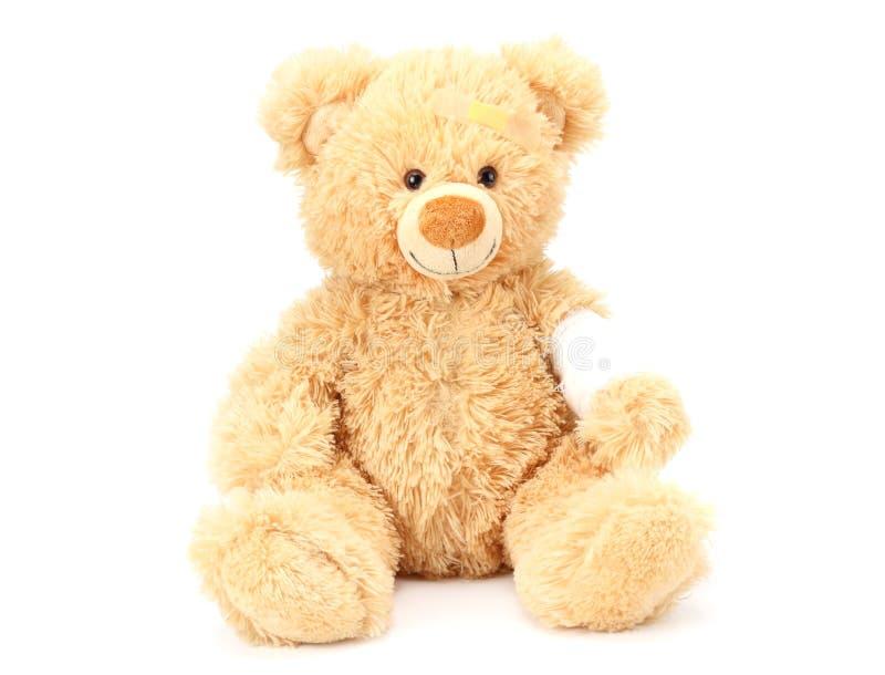 Toy teddy bear with bandage isolated on white background stock images