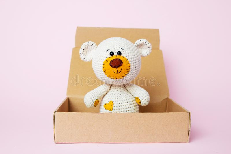 Toy teddy bear in a craft box isolated on a pink background. Baby background. Copy space, top view royalty free stock photography