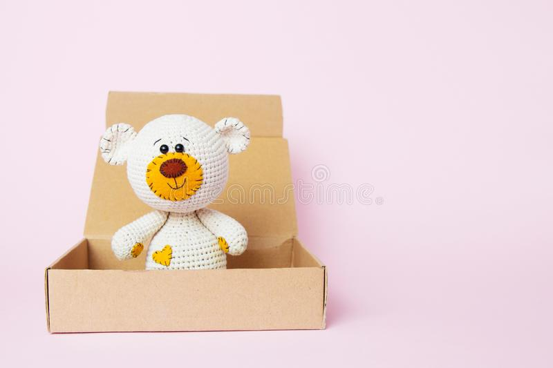 Toy teddy bear in a craft box isolated on a pink background. Baby background. Copy space, top view stock image
