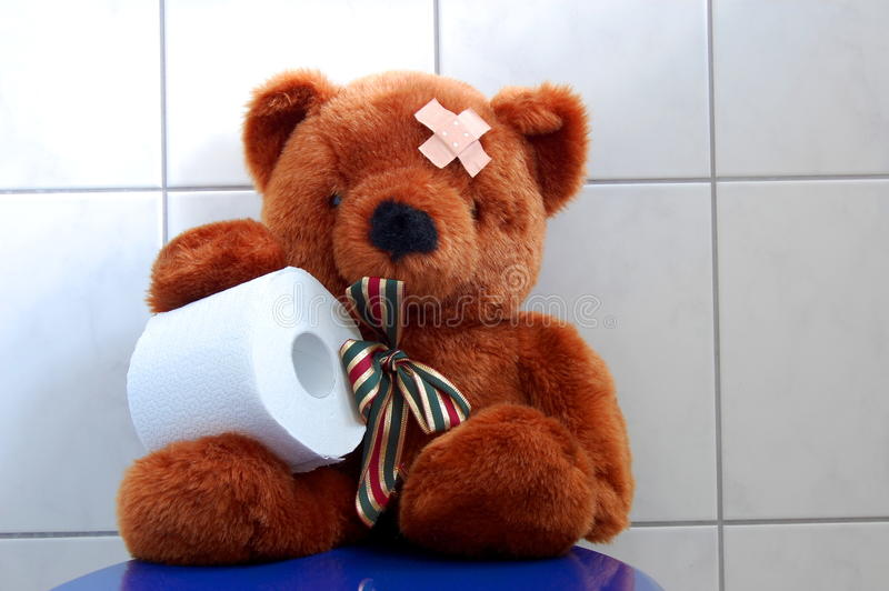 Toy teddy bear on wc toilet. Toy teddy bear with paper in the bathroom on toilet royalty free stock image