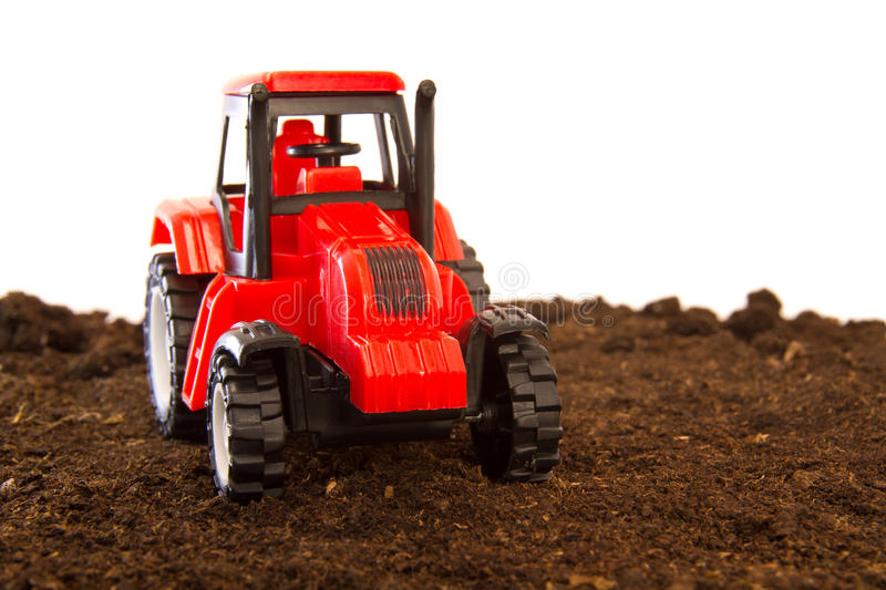 Toy tractor. On a hill garden soil stock images