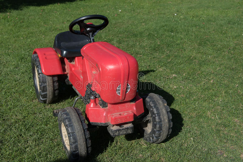 Toy tractor standing on the grass.  stock photo