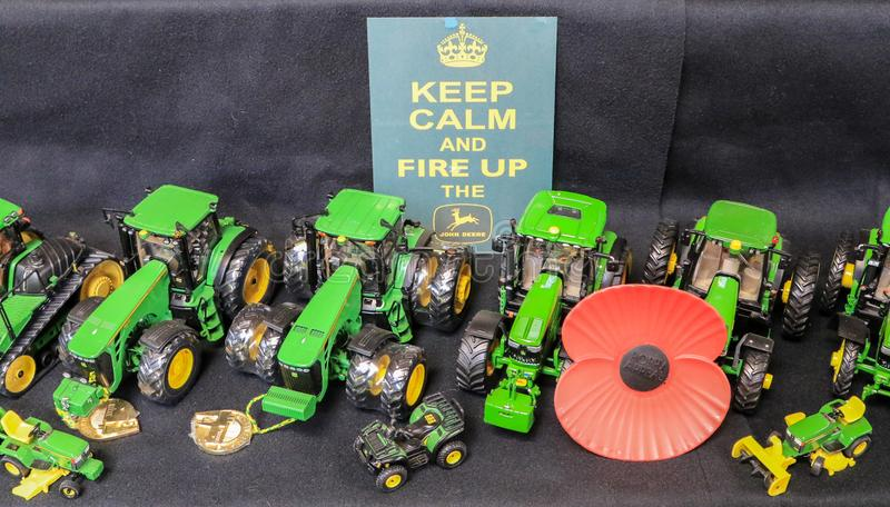 Toy tractors for sale in shop. Lots of different john Deere toy tractors on show in rows at country show with red poppy for remembrance day with a sign saying royalty free stock photo