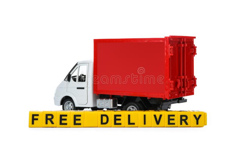 Toy truck and cubes with words FREE DELIVERY isolated. Logistics and wholesale concept. Toy truck and cubes with words FREE DELIVERY isolated on white. Logistics royalty free stock images