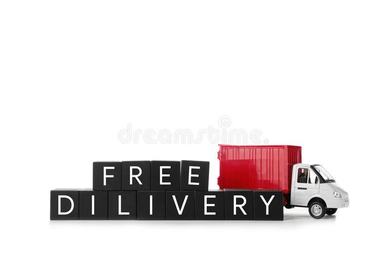 Toy truck and cubes with words FREE DELIVERY isolated. Logistics and wholesale concept. Toy truck and cubes with words FREE DELIVERY isolated on white. Logistics stock image