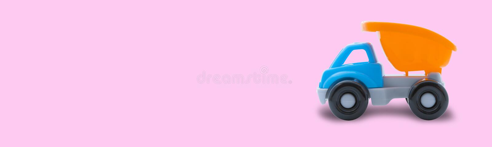 Toy truck on a pink background, space for text, concept of construction work or childish play royalty free stock photography
