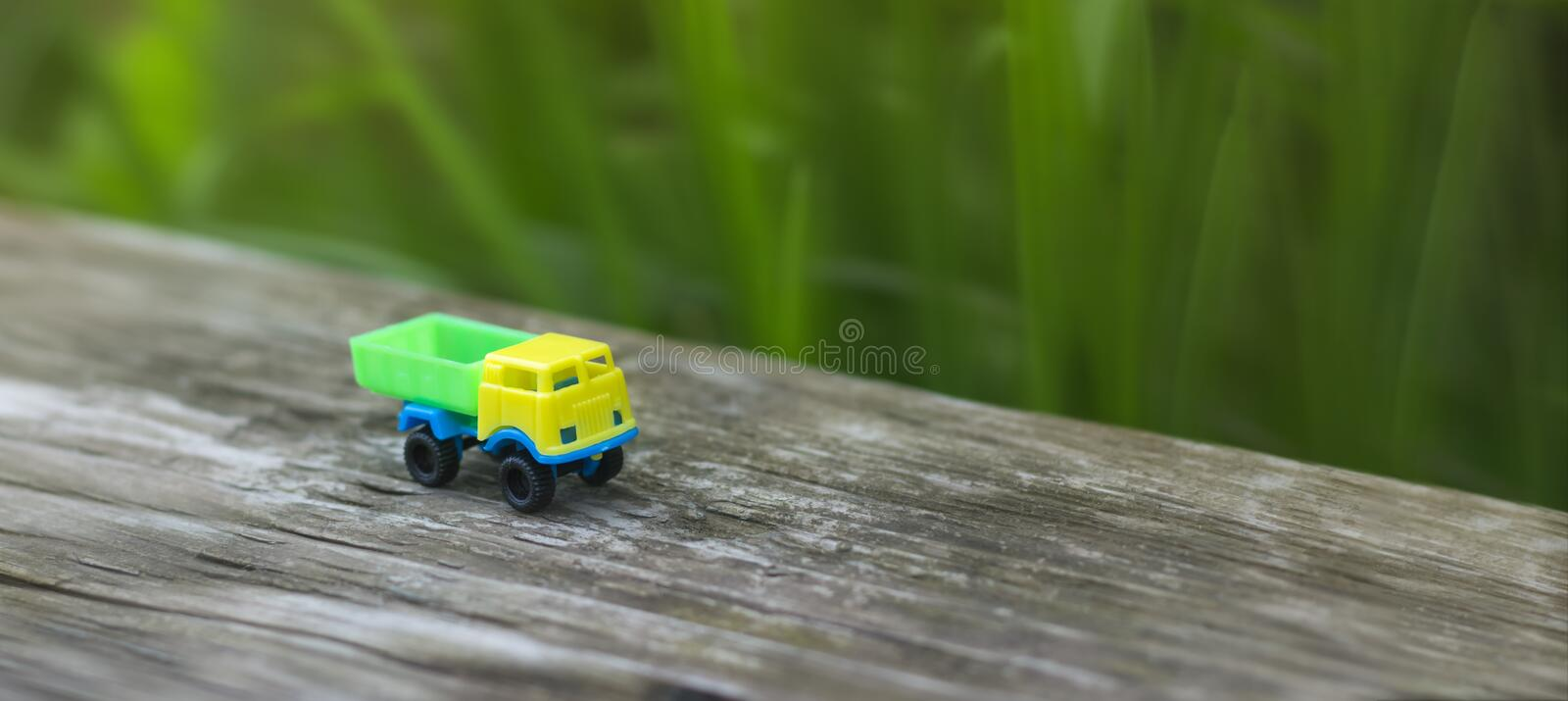 Toy truck with yellow cab and green body on wooden background with copy space stock images