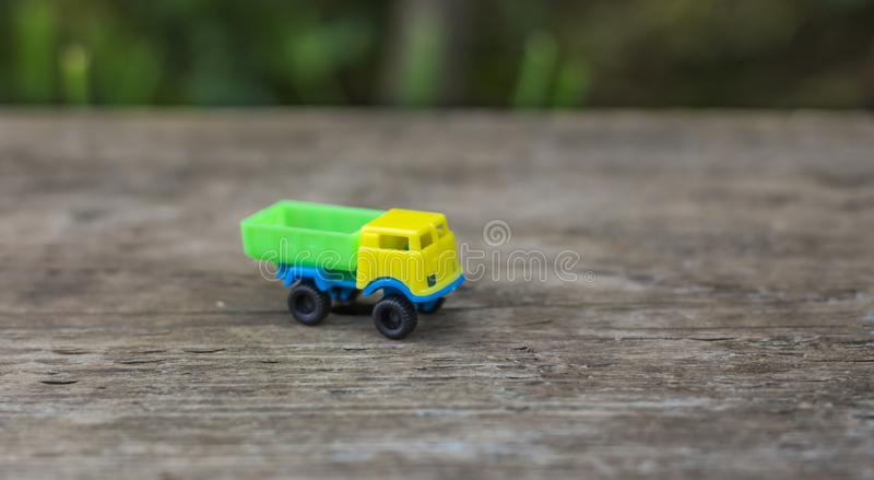 Toy truck with yellow cab and green body on wooden background royalty free stock image