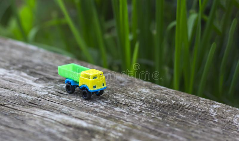 Toy truck with yellow cab and green body on wooden surface on nature background with copy space royalty free stock images