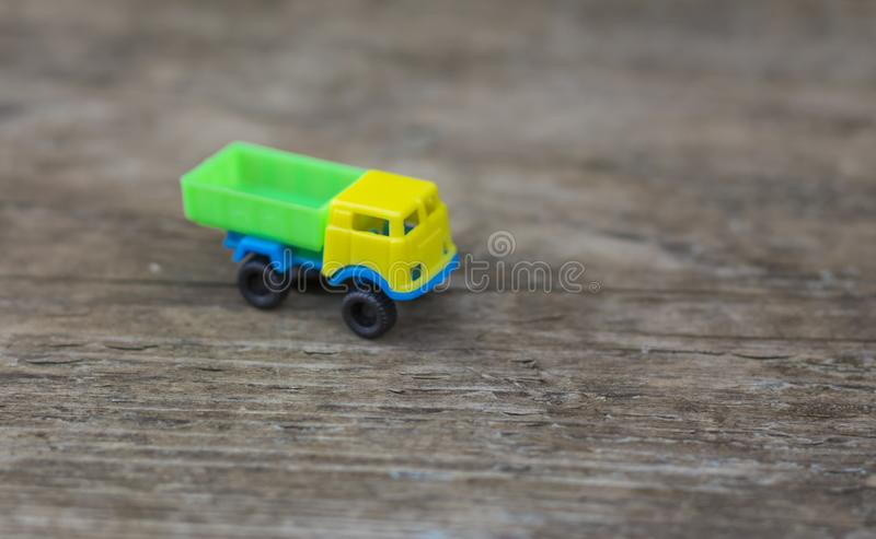 Toy truck with yellow cab on wooden background stock image