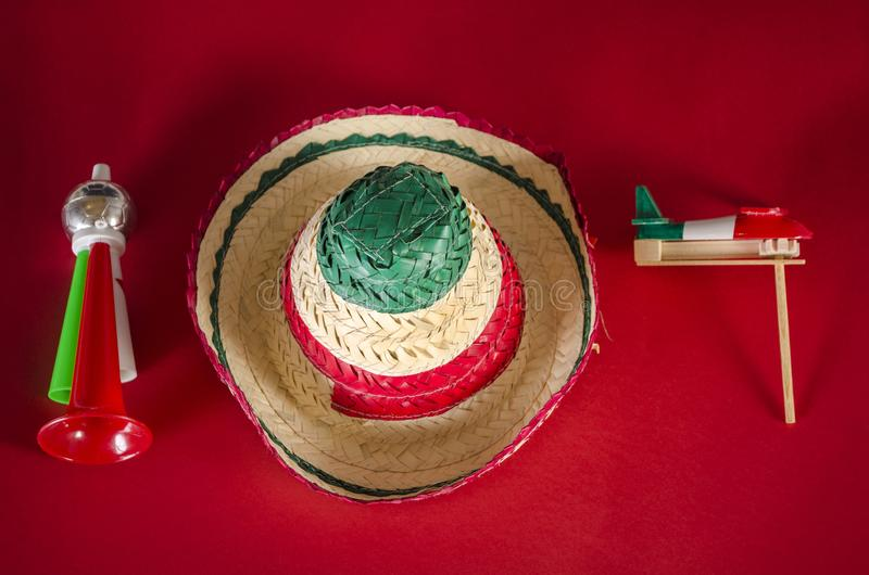 Accessories for mexican Independence Day celebration. Toy trumpet, hat and noisemaker against red background. Accessories for mexican Independence Day stock photos