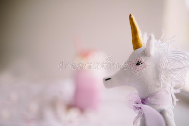 Toy unicorn on backgound of pink milk shake. Milk shake, cocktail. Unicorn coffee. Unicorn food. Soft focus stock photos