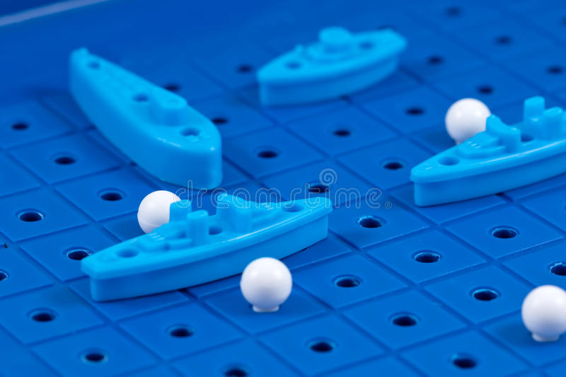 Toy war ships and a submarine lined up to play a Board game. Toy destroyer surrounded by a corridor of underwater mines royalty free stock photo