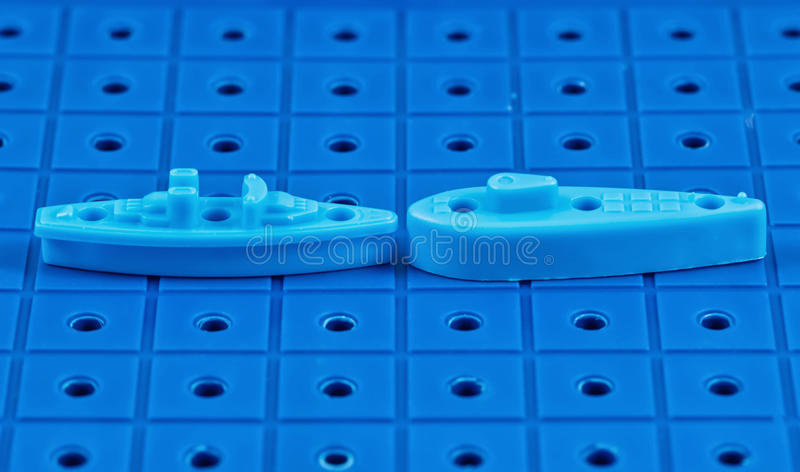 Toy war ships and a submarine lined up to play a Board game. Toy destroyer surrounded by a corridor of underwater mines royalty free stock photography