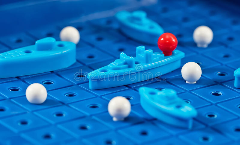 Toy war ships and submarine are placed on the blue playing Boar. Toy war ships and submarine are placed on the playing Board in the game battleship royalty free stock image