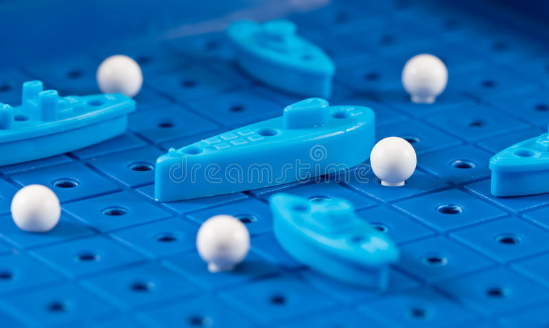 Toy war ships and submarine are placed on the blue playing Boar. Toy war ships and submarine are placed on the playing Board in the game battleship royalty free stock images