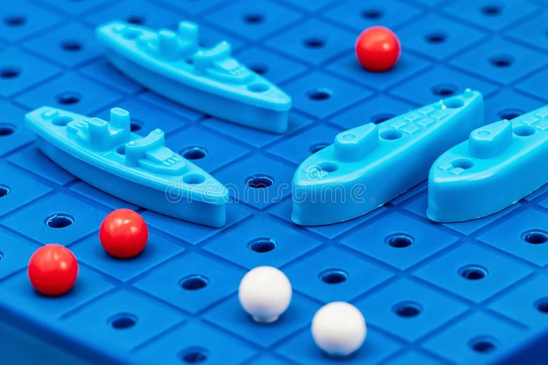 Toy war ships and submarine are placed on the blue playing Board. Toy war ships and submarine are placed on the playing Board in the game battleship royalty free stock photography