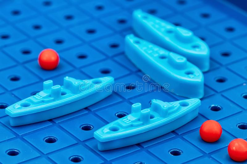Toy war ships and submarine are placed on the blue playing Board. Toy war ships and submarine are placed on the playing Board in the game battleship stock photo