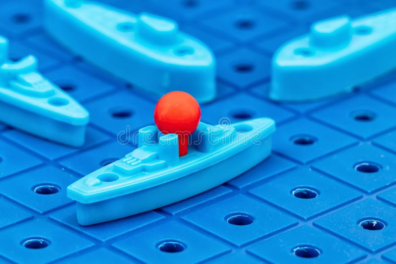 Toy war ships and submarine are placed on the blue playing Board. Toy war ships and submarine are placed on the playing Board in the game battleship royalty free stock images