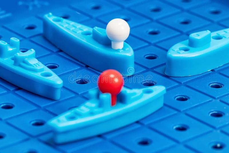 Toy war ships and submarine are placed on the blue playing Board. Toy war ships and submarine are placed on the playing Board in the game battleship stock photography