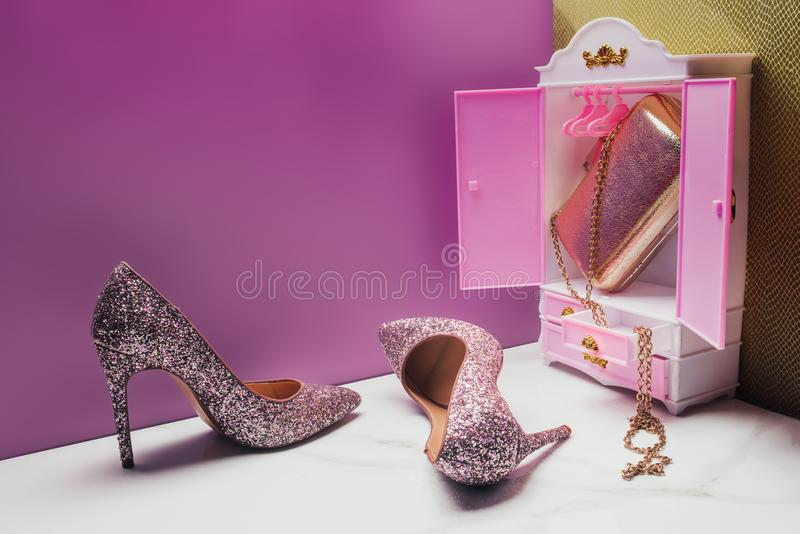 Toy wardrobe with real size shiny high heels and handbag in miniature. Pink room stock image