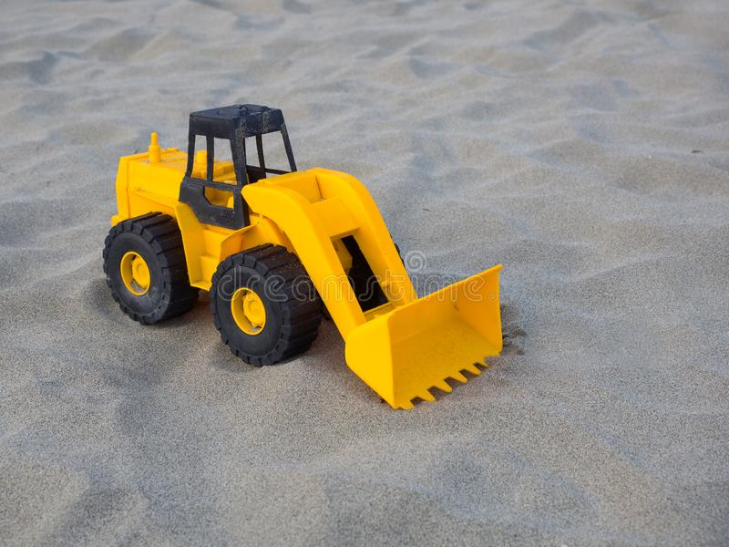 Toy wheel loader excavator on the sand at the beach royalty free stock photos