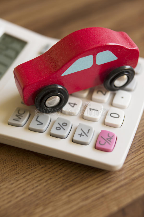 Toy Wooden Car On Calculator Rouge Pour Illustrer Le Coût De Circuler En Voiture Photo stock