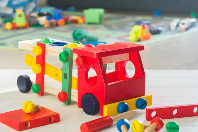 Toy wooden car constructor in children`s room. Selective focus. Preschool education concept with colorful details.  royalty free stock photos