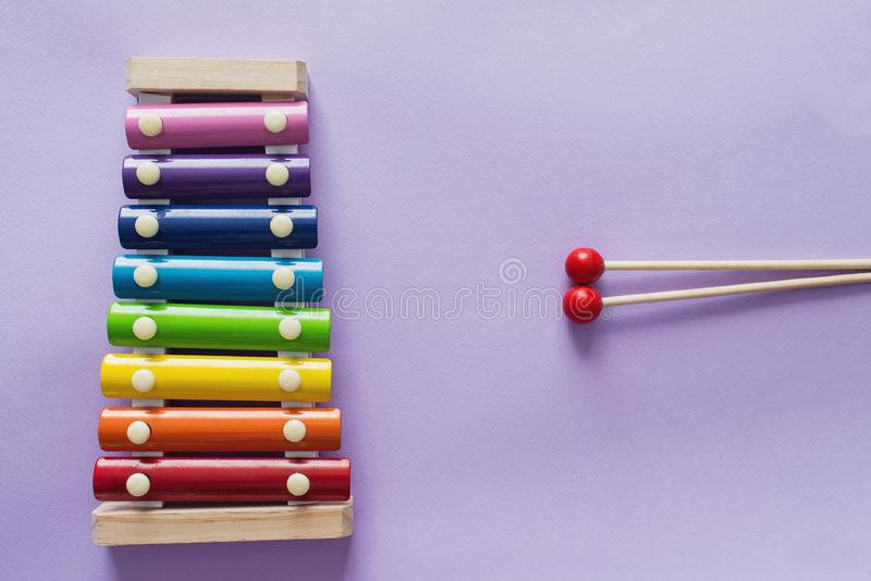 A toy wooden colorful xylophone on purple background with copy space. Children`s toy and musical instrument. Music and childhood. Concept stock photo