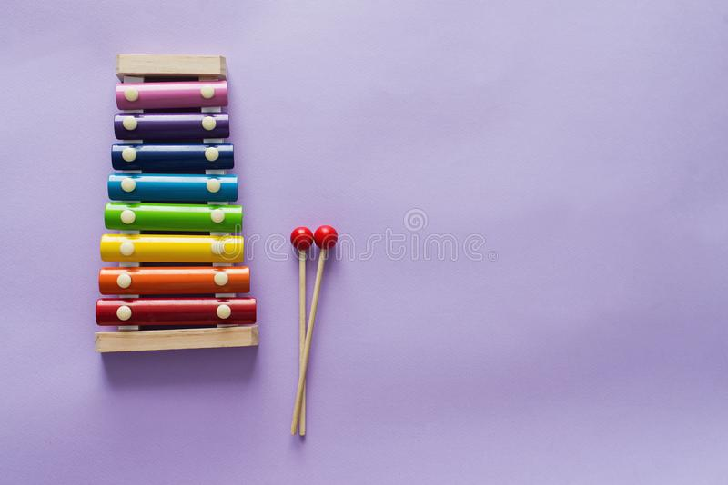 A toy wooden colorful xylophone on purple background with copy space. Children`s toy and musical instrument. Music and childhood. Concept royalty free stock photo