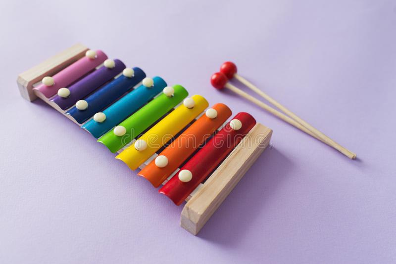 A toy wooden colorful xylophone on purple background with copy space. Children`s toy and musical instrument. Music and childhood. Concept royalty free stock photos