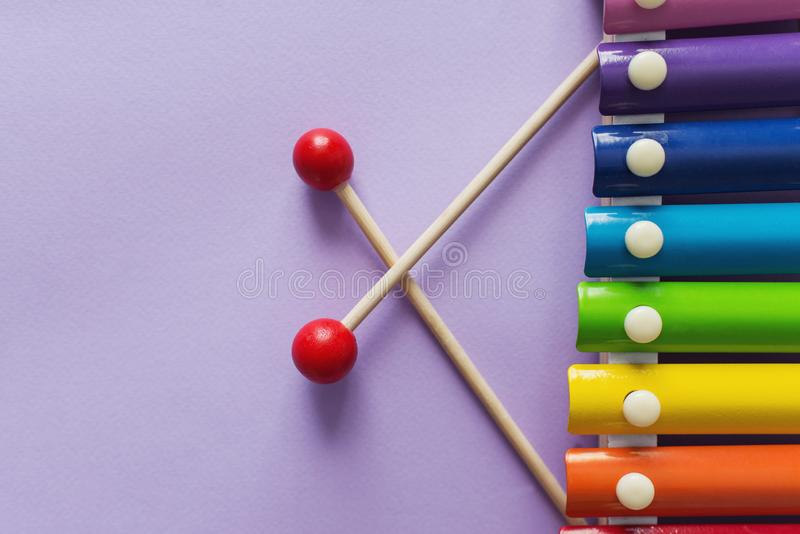 A toy wooden colorful xylophone on purple background with copy space. Children`s toy and musical instrument. Music and childhood. Concept royalty free stock image
