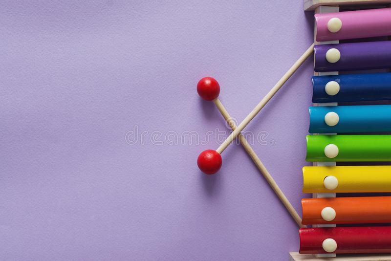 A toy wooden colorful xylophone on purple background with copy space. Children`s toy and musical instrument. Music and childhood. Concept royalty free stock photography