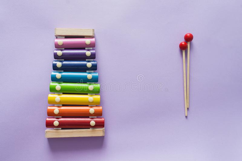 A toy wooden colorful xylophone on purple background with copy space. Children`s toy and musical instrument. Music and childhood. Concept stock photography